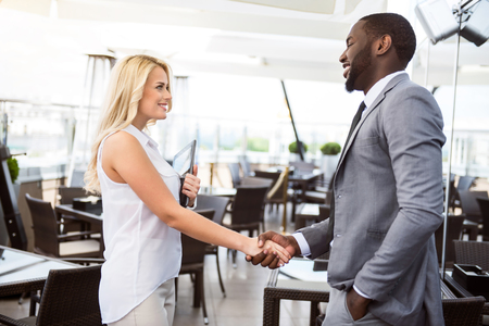 gladness: Nice to work with you. Positive cheerful professional colleagues looking at each other and shaking hands while expressing gladness Stock Photo