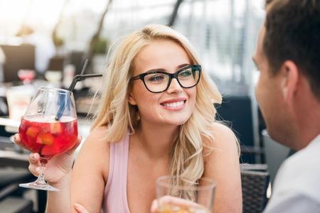 voluptuosa: el vistazo magnético. alegre agradable voluptuosa mujer cóctel beber y hablar con su novio mientras descansa en el café Foto de archivo
