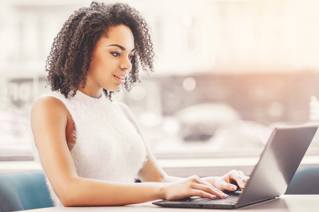Hard work ensures success. Concentrated and smiling young african women working on laptop while sitting at working place Stock Photo