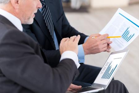 diligente: trabajadores diligentes. hombres de negocios profesionales que se sientan en el sof� y de trabajo con los papeles mientras se discute proyecto Foto de archivo