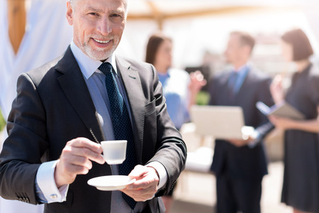 drink me: Join me. Positive delighted smiling handsome man holding cup of coffee and going to drink it while his colleagues talking in the background Stock Photo