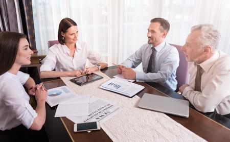 cooperativismo: El trabajo cooperativo. Agradables colegas encantados alegre que habla y que se sientan en la mesa mientras se trabaja en conjunto