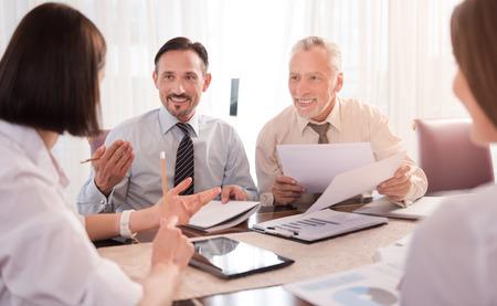 Conseil d'administration. collègues souriants gais agréables travaillant avec des papiers et en discutant projet alors qu'il était assis à la table Banque d'images - 59828865