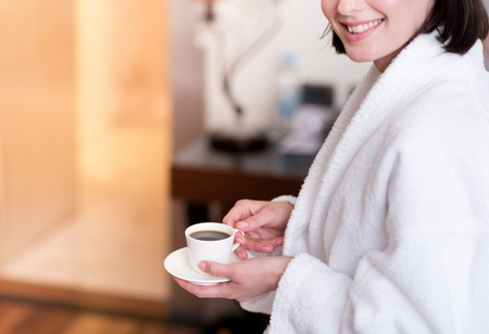 gladness: Unforgettable taste. Cheerful delighted smiling woman sitting on the bed and drinking coffee while expressing gladness