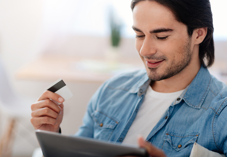 easier: Make it easier. Cheerful handsome man smiling and using tablet while holding credit card Stock Photo