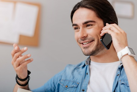 expressing joy: Lively discussion. Positive delighted handsome man holding cell phone and talking on it while expressing joy Stock Photo