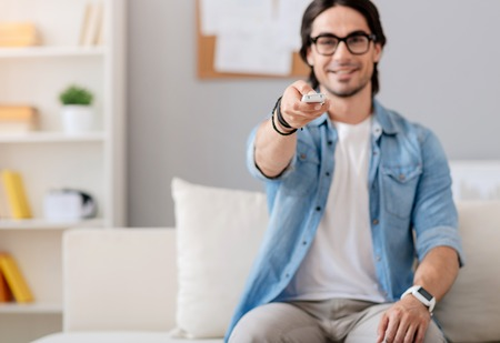 Switch it on. Pleasant handsome positive man sitting on the couch and holding remote control while watching TV Stock Photo