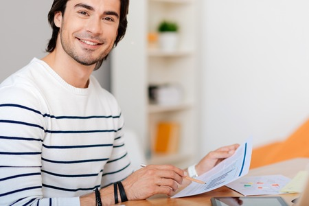 working hours: Working hours. Cheerful bearded man smiling and holding papers while sitting at the table in the office