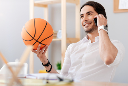 expressing joy: Lead active life. Cheerful handsome smiling man talking on cell phone and expressing joy while holding basket ball Stock Photo