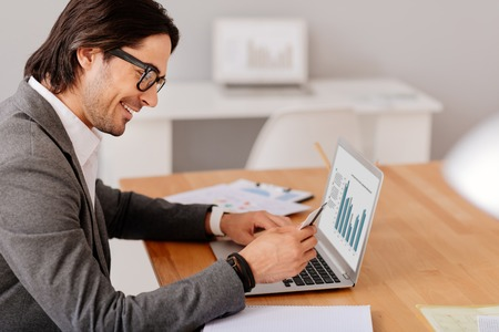 overjoyed: Joy in mind. Overjoyed smiling handsome man sitting at the table and holding credit card while using laptop
