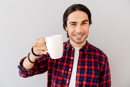 booster: Energy booster. Positive handsome emotional man holding cup and drinking coffee while standing isolated on grey background