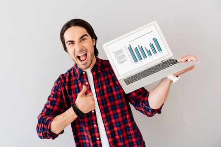 overjoyed: Best model. Overjoyed smiling handsome man holding laptop and thumbing up while standing isolated on grey background