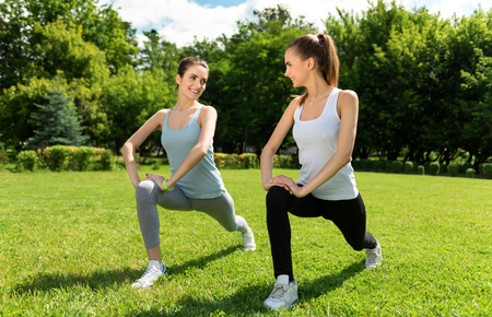 tempo: Keep the tempo. Cheerful happy young women stretching and doing sport exercises outdoors