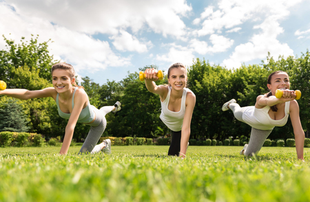 to move forward: Move forward. Positive overjoyed smiling charming women holding dumbbells and doing sport exercises while expressing gladness