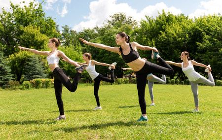 activate: Activate your muscles. Pleasant delighted smiling women holding their legs and expressing positivity while doing sport exercises outside