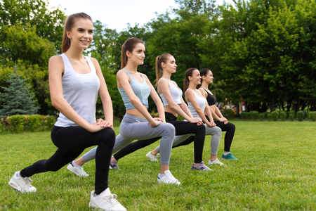 gladness: Safe and sound. Positive beautiful smiling women stretching and doing sport activities while expressing gladness