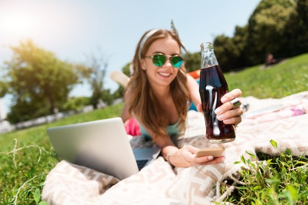 cola bottle: Favorite drink. Cheerful and smiling young woman holding cola bottle and her smart phone while lying on the grass in the park