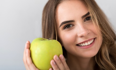 expressing joy: My favorite. Portrait of pleasant cheerful beautiful woman holding an apple and smiling while expressing joy