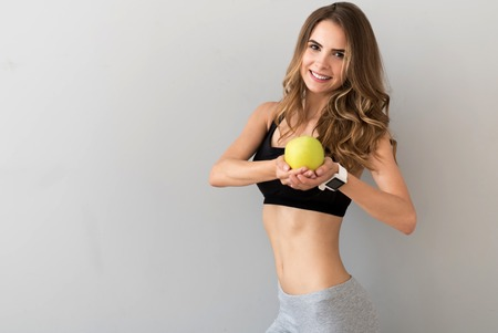 excess weight: My remedy. Positive charming young woman holding an apple and smiling while feeling content