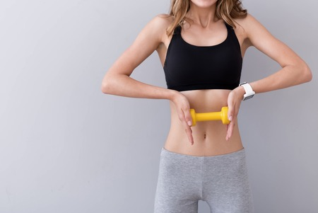 dumb bells: No day without sport. Pleasant young slim woman holding dumb bells and doing exercises while standing isolated on grey background Stock Photo