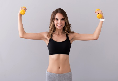 dumb bells: Joyful activities. Pleasant beautiful cheerful woman holding dumb bells and doing exercises while smiling on grey background