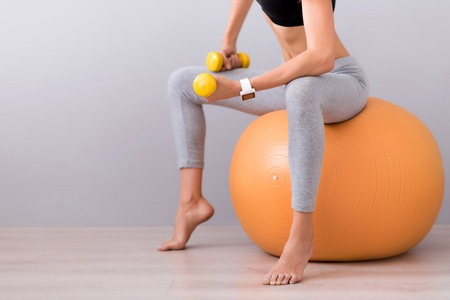 dumb bells: Stay in shape. Pleasant slim woman sitting on the rubber ball and using dumb bells while doing sport exercises