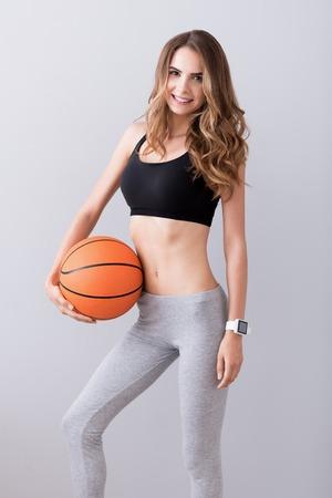 potěšen: Připraven hrát. Příjemná veselá štíhlá žena drží míč a usmívá se při hraní basketbalu