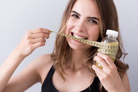 kilos: Get rid of extra kilos. Cheerful nice sporty woman holding measure type in her mouth and keeping bottle of juice while expressing joy