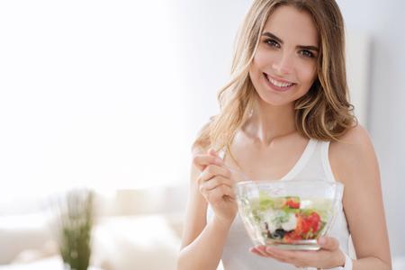 Lo que nee para estar sano. Agradable deleitó mujer alegre sonriente y comer ensalada de verdura sabrosa al tiempo que expresa alegría