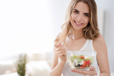 to be pleasant: What I nee to be healthy. Pleasant delighted cheerful woman smiling and eating tasty vegetable salad while expressing joy
