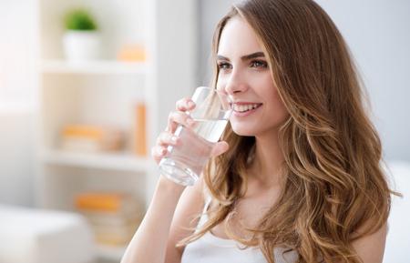 potěšen: Moje dávka pozitivity. Veselá radost krásná žena drží sklenici a pitné vody, zatímco se usmívá