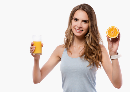 brighten: Brighten up your routine. Cheerful delighted beautiful woman holding orange and glass of juice while standing isolated on white background