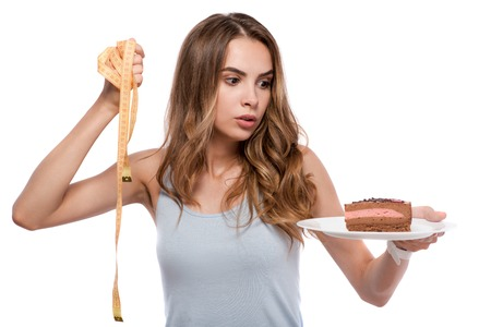 baffled: Real dilemma. Pleasant baffled woman holding plate with cake and measure tape and choosing between them while standing isolated on white background