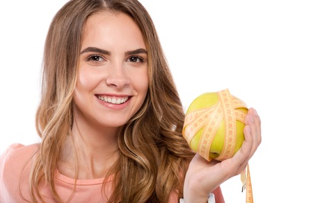 Full of energy. Portrait of cheerful nice woman smiling and holding apple while standing isolated on white background Stock Photo