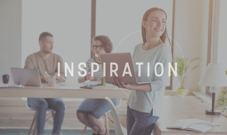 Inspire yourself. Inspirational typographic message for inspiration with image of young smiling businesswoman holding laptop in a background Stock Photo