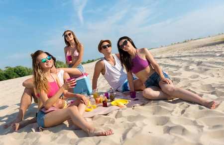 Nice time together, Cheerful delighted smiling friends sitting on the sand and having a picnic while resting on the beach