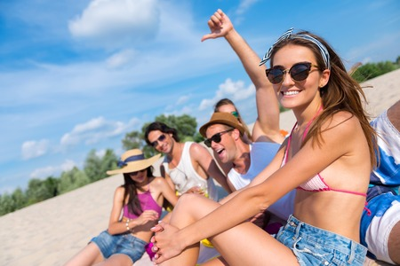 express feelings: express your feelings. Cheerful smiling friends sitting on the sand and having fun while enjoying the picnic Stock Photo
