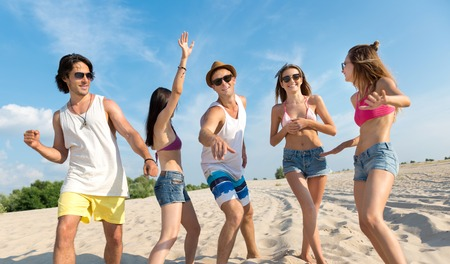 reckless: Just dance. Cheerful smiling reckless friends standing on the beach and having fun while expressing gladness