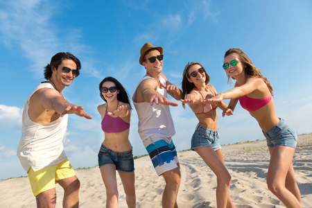 reckless: Share our emotions. Positive delighted smiling friends standing on the beach and holding hands in front of them while resting together