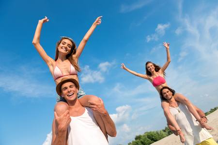 overjoyed: Feel the taste of summer. Pleasant overjoyed smiling men holding beautiful girls on the shoulders while having fun on the beach