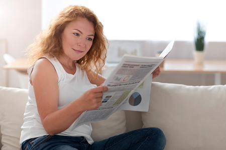 interested: Involved in world of news. Pleasant delighted interested adult woman reading newspaper and sitting on the sofa while resting at home Stock Photo