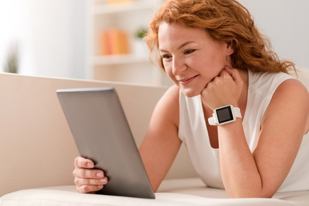 gladness: Find inspiration. Positive delighted adult woman using tablet and expressing gladness while lying on the sofa