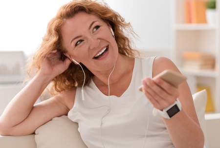 Feel the bite. Joyful adult smiling woman listening to music and holding cell phone while resting on the couch