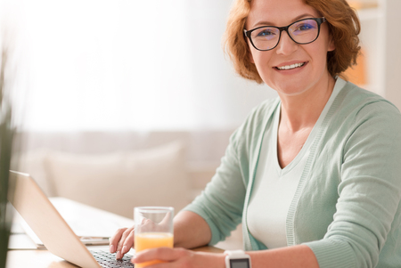 Share positivity. Joyful smiling senior woman sitting at the table and drinking juice while using laptop