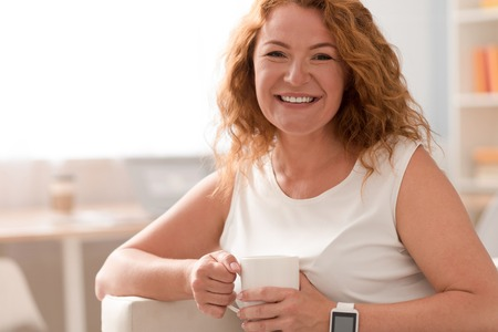 Full of gladness. Cheerful delighted smiling woman holding cup and drinking coffee while sitting on the couch