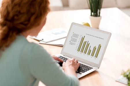 diligente: trabajador diligente. mujer involucrada agradable trabajar en el ordenador portátil y sentado en la mesa Foto de archivo