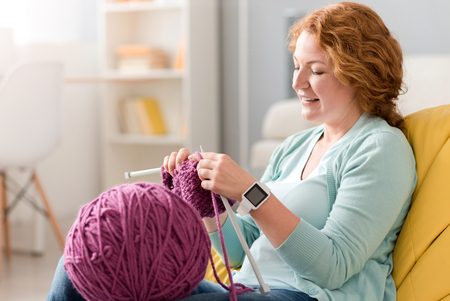 best way: Best way to relax. Pleasant delighted beautiful senior woman sitting on the sofa and holding needles while knitting