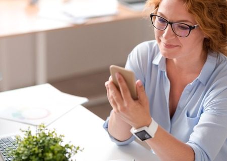 Modern user. Cheerful delighted beautiful senior woman sitting at the table and expressing gladness while using cell phone