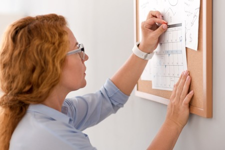 Mind the dates. Pleasant busy woman holding calendar and sticking it to the board while working