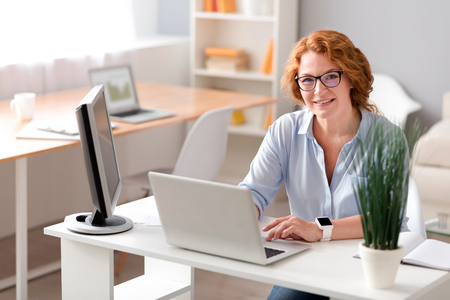 My workplace. Pleasant delighted senior woman sitting at the table and using laptop while being involved in work Stock Photo